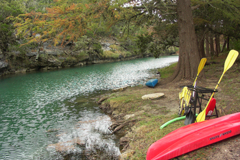 a beautiful view of a riverbank and the river that flows through the HEB preserve/camp area.  a kayak and conoe on the bank